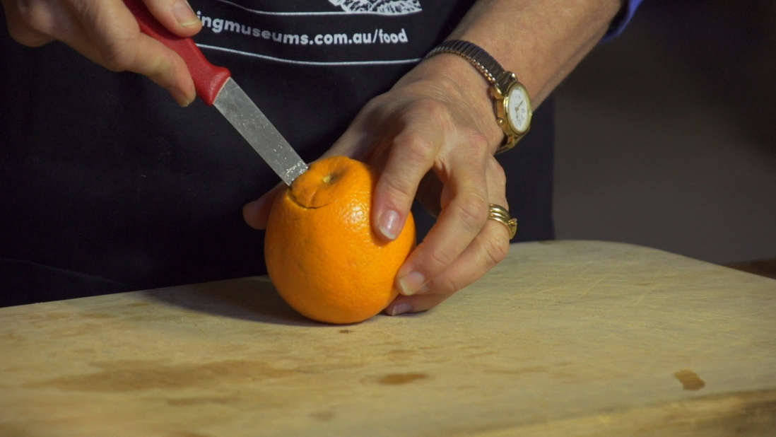 Knife being inserted into skin of orange.