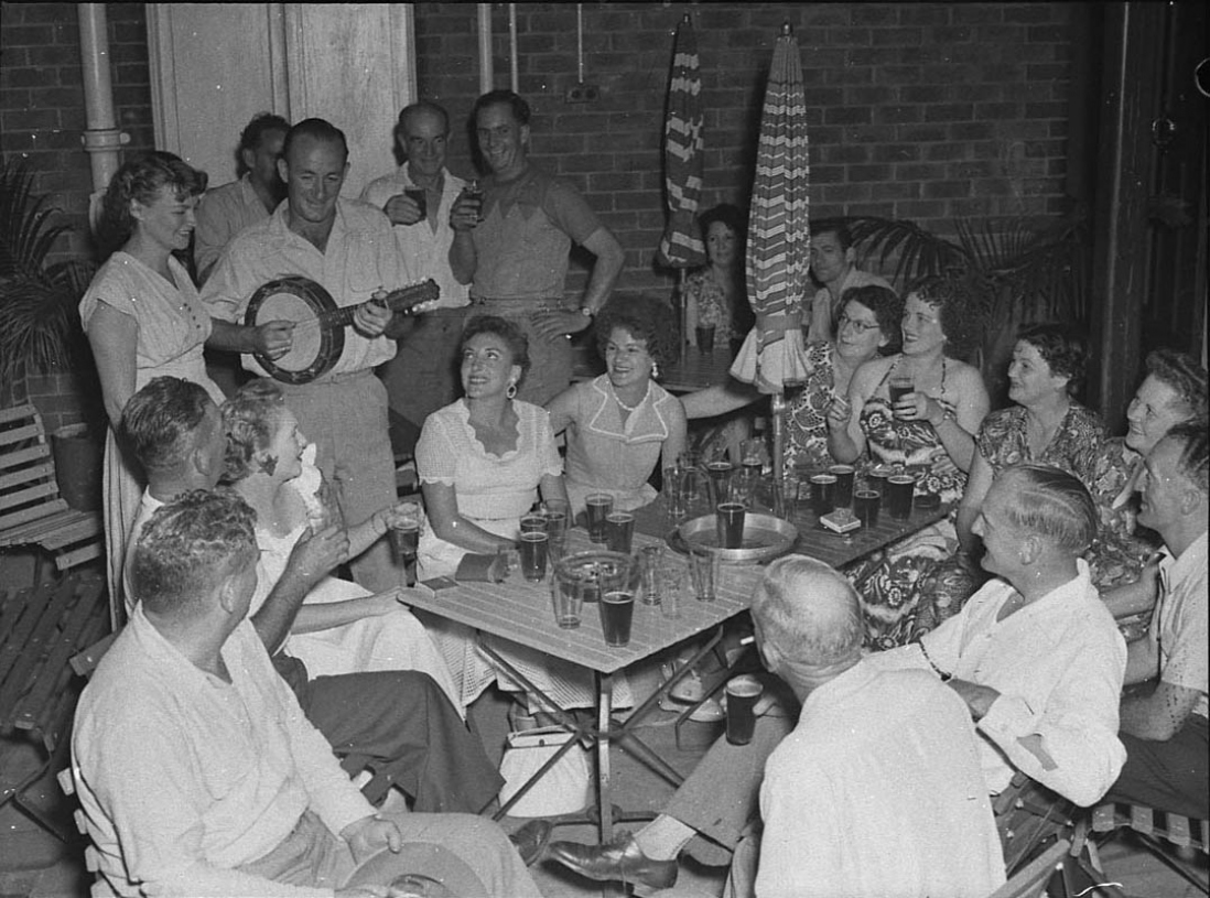 A happy group of drinkers gather around a table in what looks like a pub beer garden. A man in the back plays a banjo.