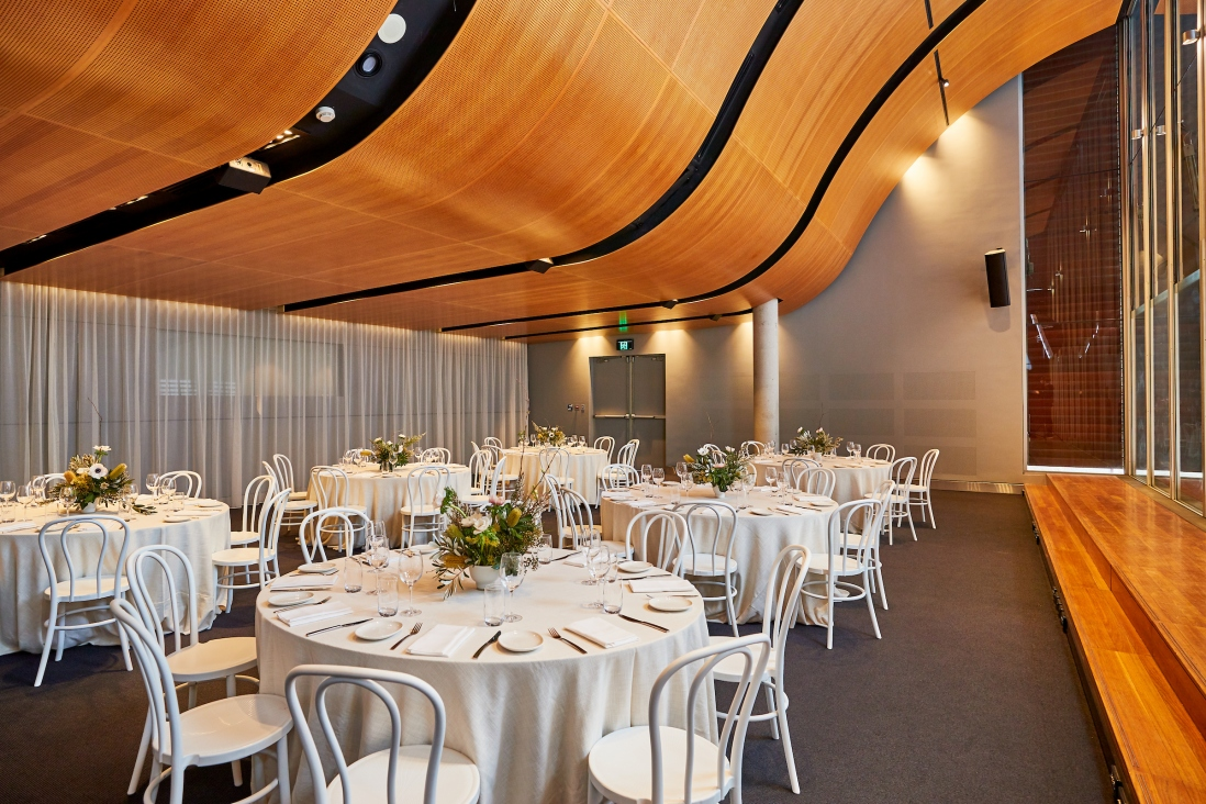 Tables set with floral displays for function in room with curved wooden ceiling.