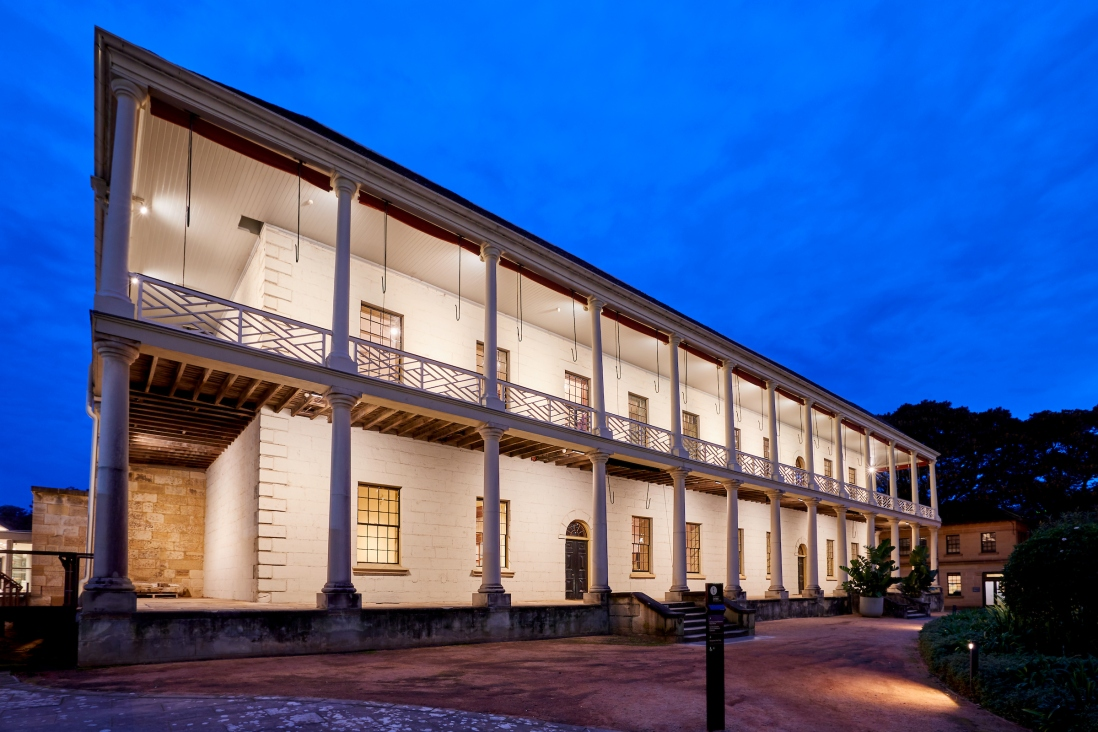 Two storey colonial era building with verandah lit up at night time.