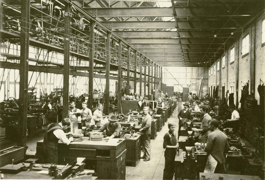 Large workshop with rows of benches and men standing at them making tram components.