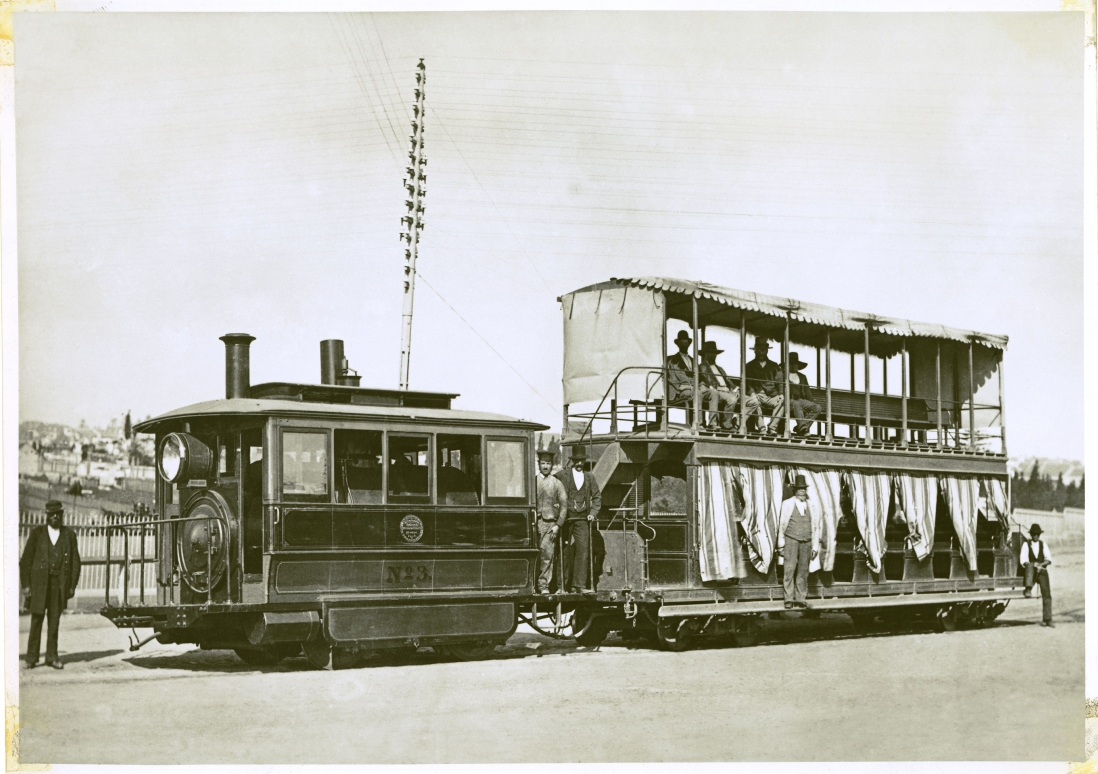 Photograph of tram with elaborate two level trailer decorated with flowing curtains.