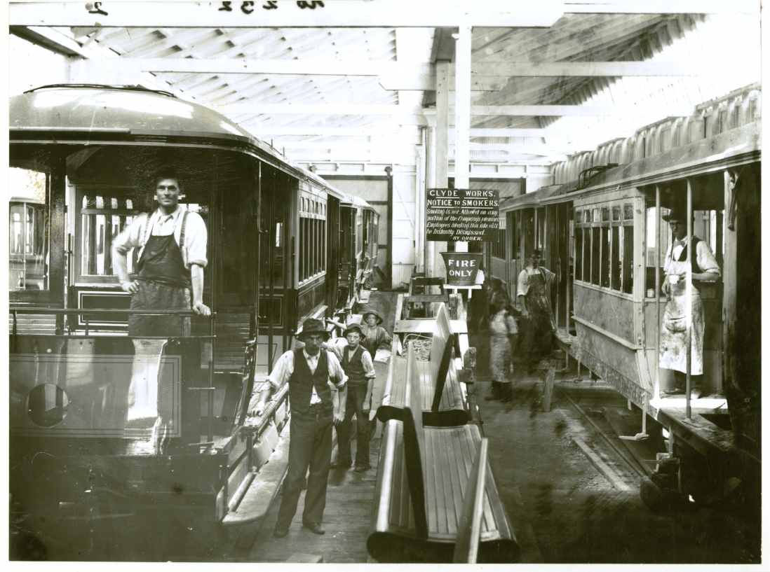 Trams being built in a workshop. Some of the numerous workers gather around looking at the camera.