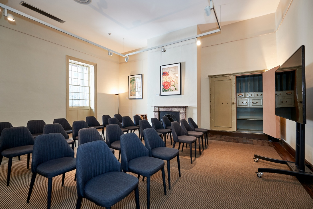 High ceilinged room set up for presentation with chairs.