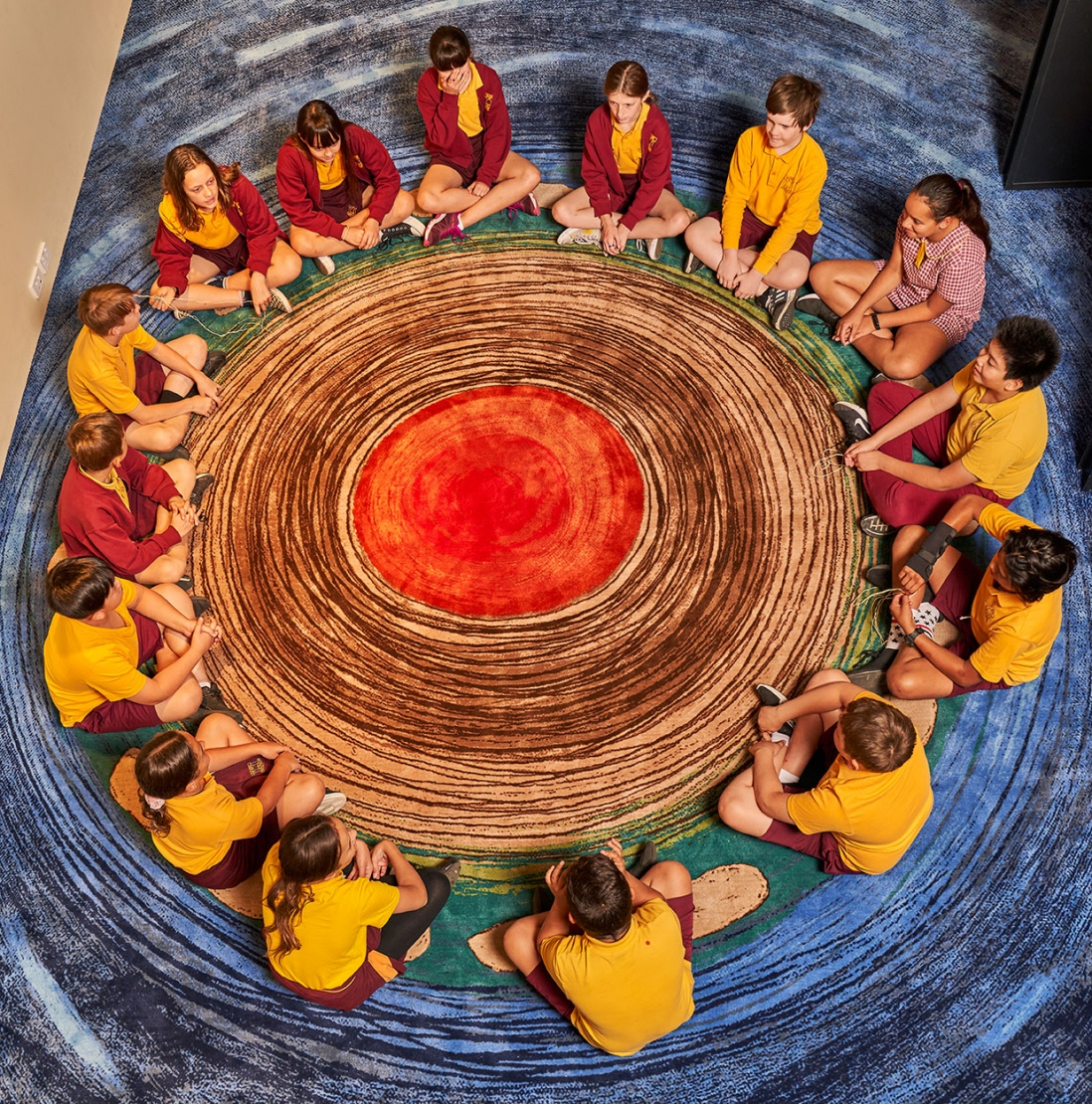 Students seated around circular painted pattern on floor.