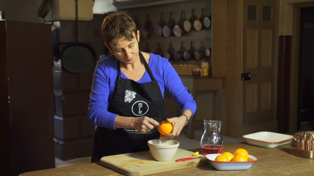 Woman carving out orange flesh into bowl.