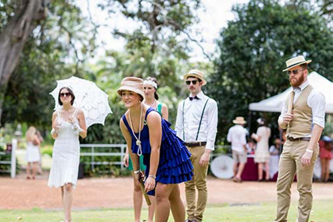 Bearded man in straw boater playing KUBB on the Carriage Loop with three women dressed in vintage fashion looking on.