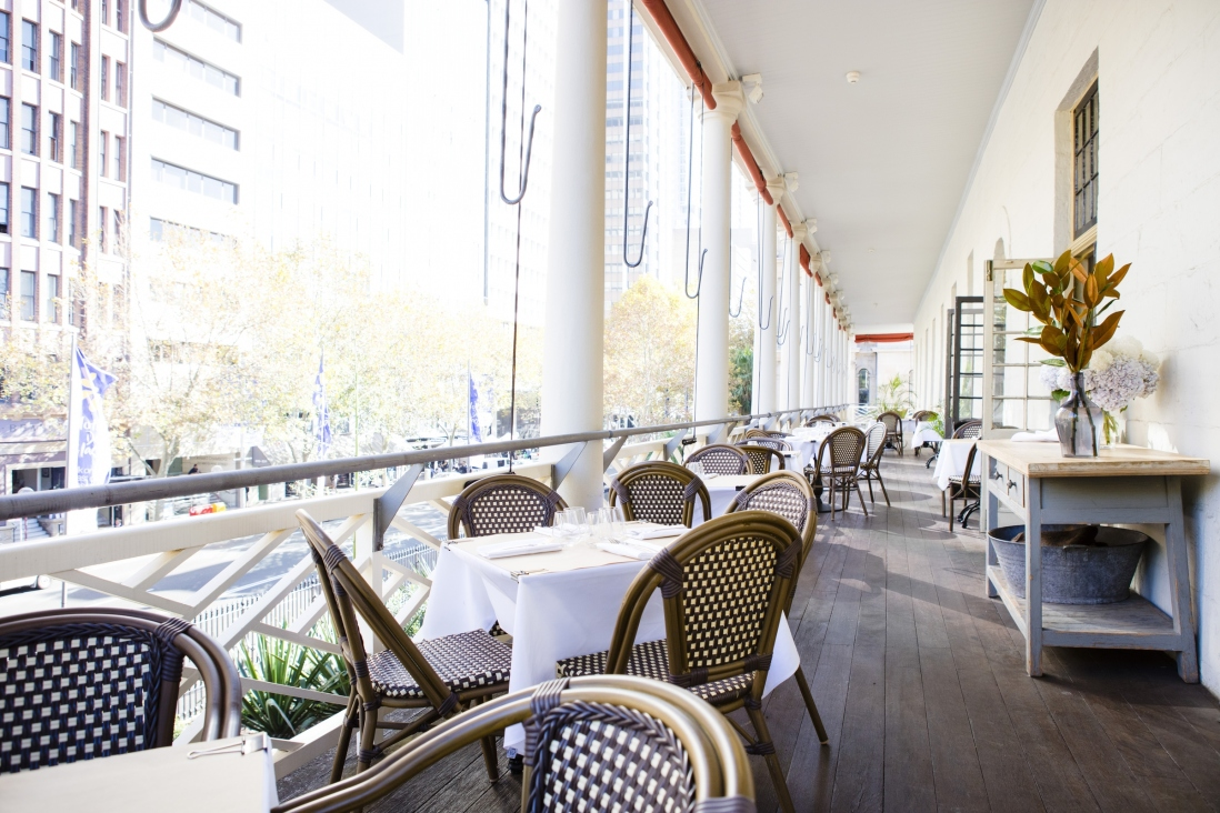 Restaurant seating on open verandah area with view of city buildings across road.