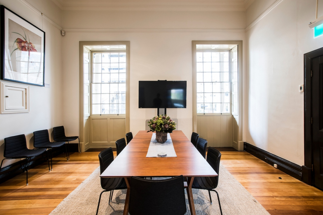 Interior of room with long meeting table flanked by two windows, with screen in middle of view.