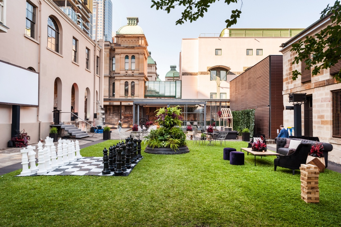 Green grassy courtyard with furniture on lawn, surrounded by buildings of different heights.