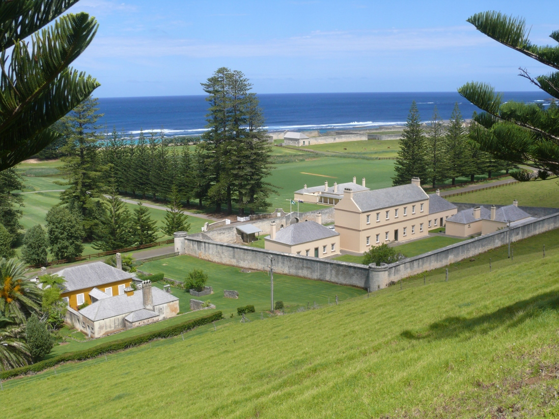 Panoramic view down green grassy slopes towards a series of convict buildings, one of which is enclosed inside a perimeter wall. Surrounding the compound is grassy open fields, paddocks and pine trees, with the blue ocean and sky beyond.