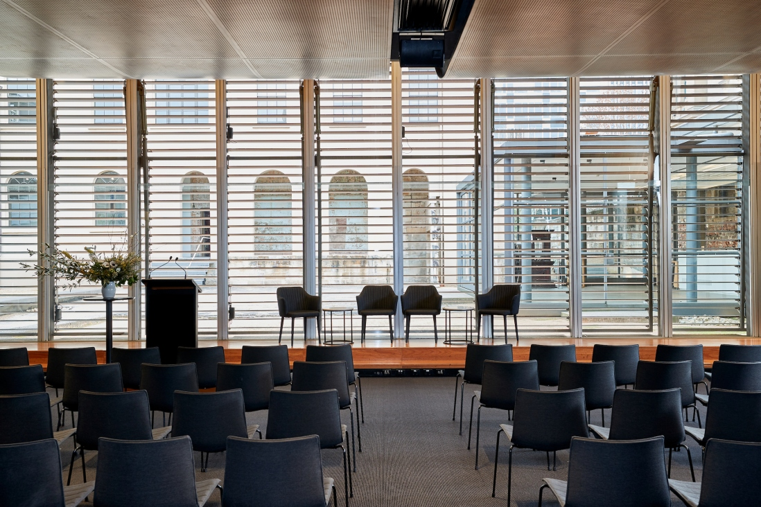 View of large conference room looking towards raised platform and  semi-shuttered windows behind chairs.