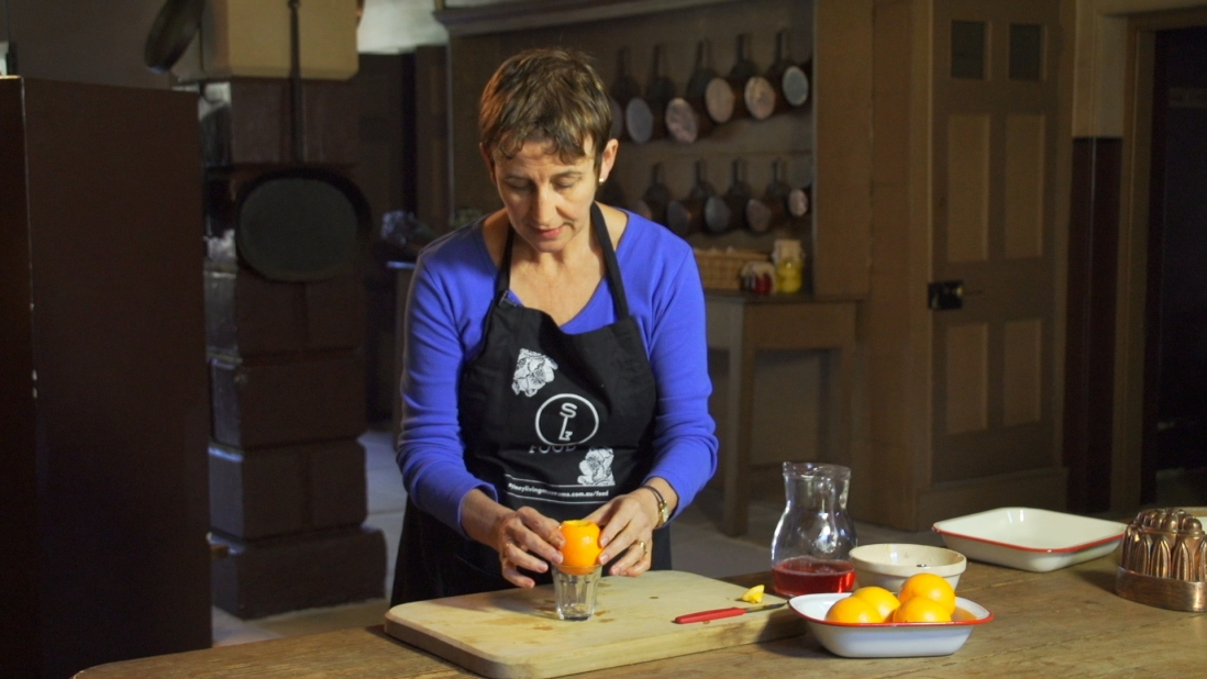 Woman placing hollowed orange in teacup.
