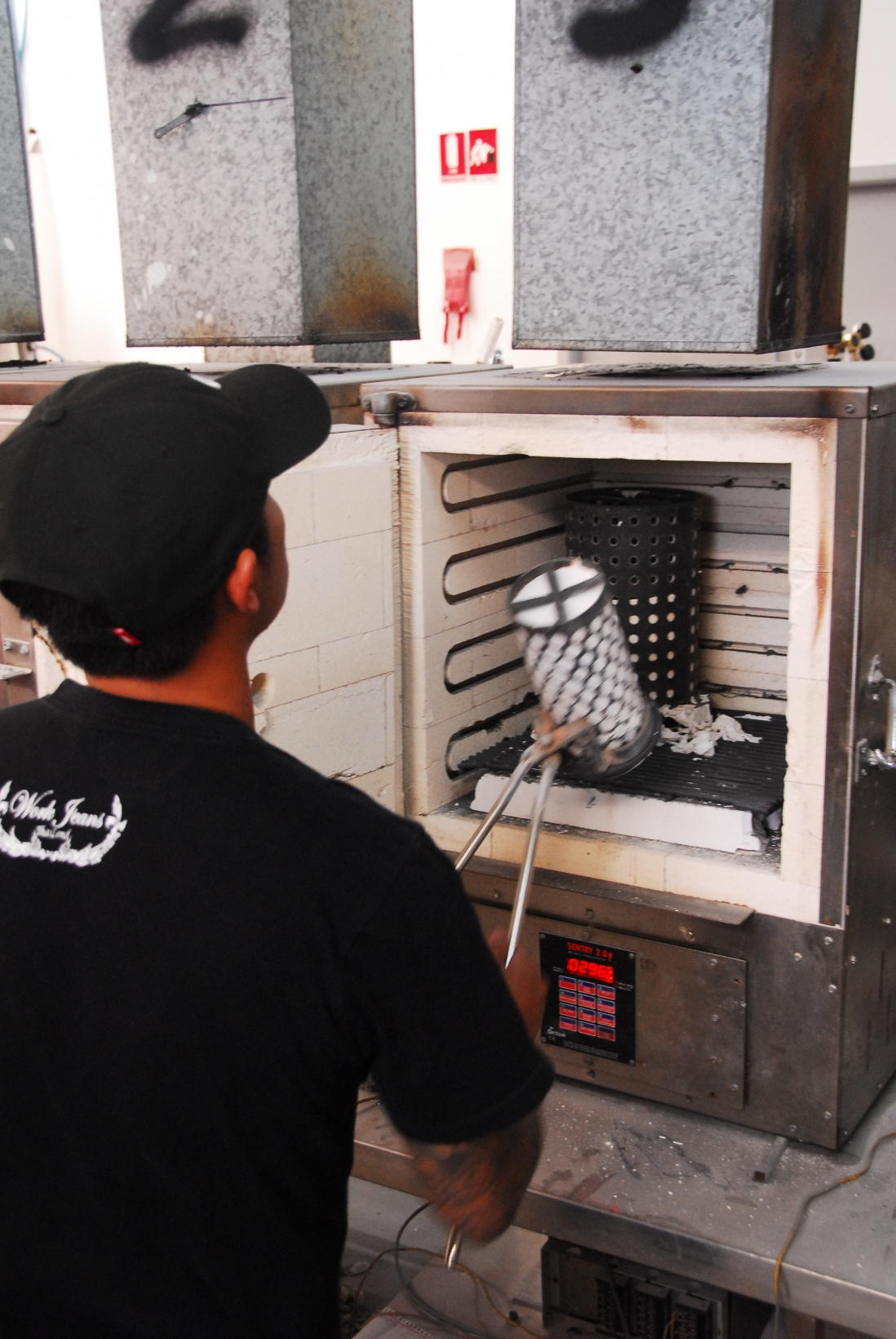 Man in cap at open door of industrial oven handling cylindrical object with tongs.