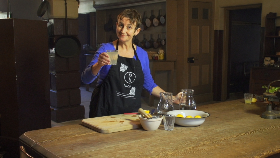 Woman in blue apron with lemonade and ingredients on wooden table in front of her.