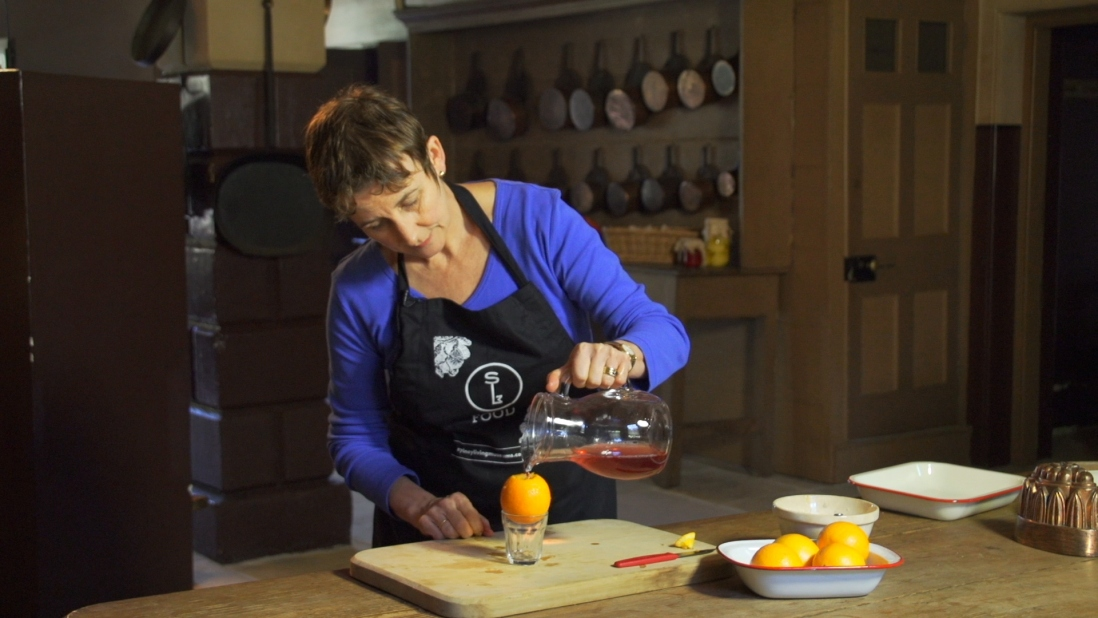Woman pouring liquid jelly into hollowed orange.