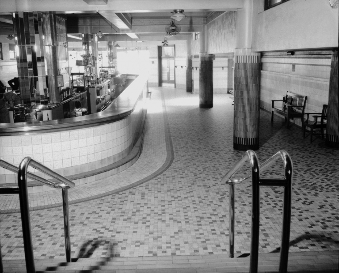 Pub interior showing large open tiled expanse with a long bar to the left