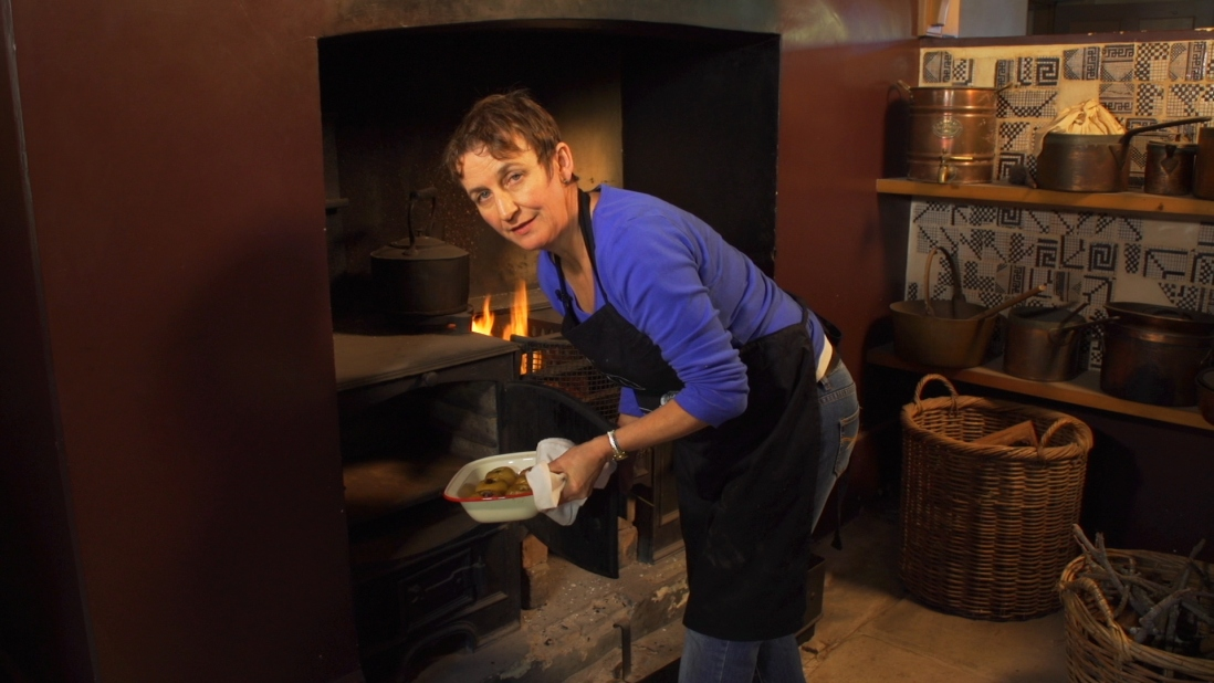 Woman in front of fire bending down with baking dish to be placed into oven.