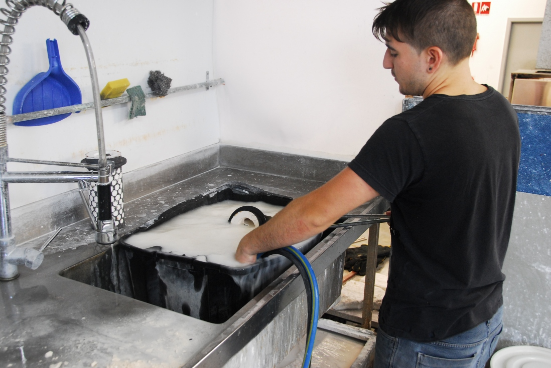 Man with hose washing item in large industrial tub full of white liquid.