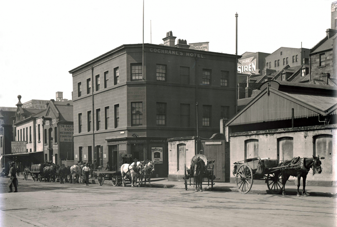 Black and white image of three story corner building with a line of horses and carts waiting outside.