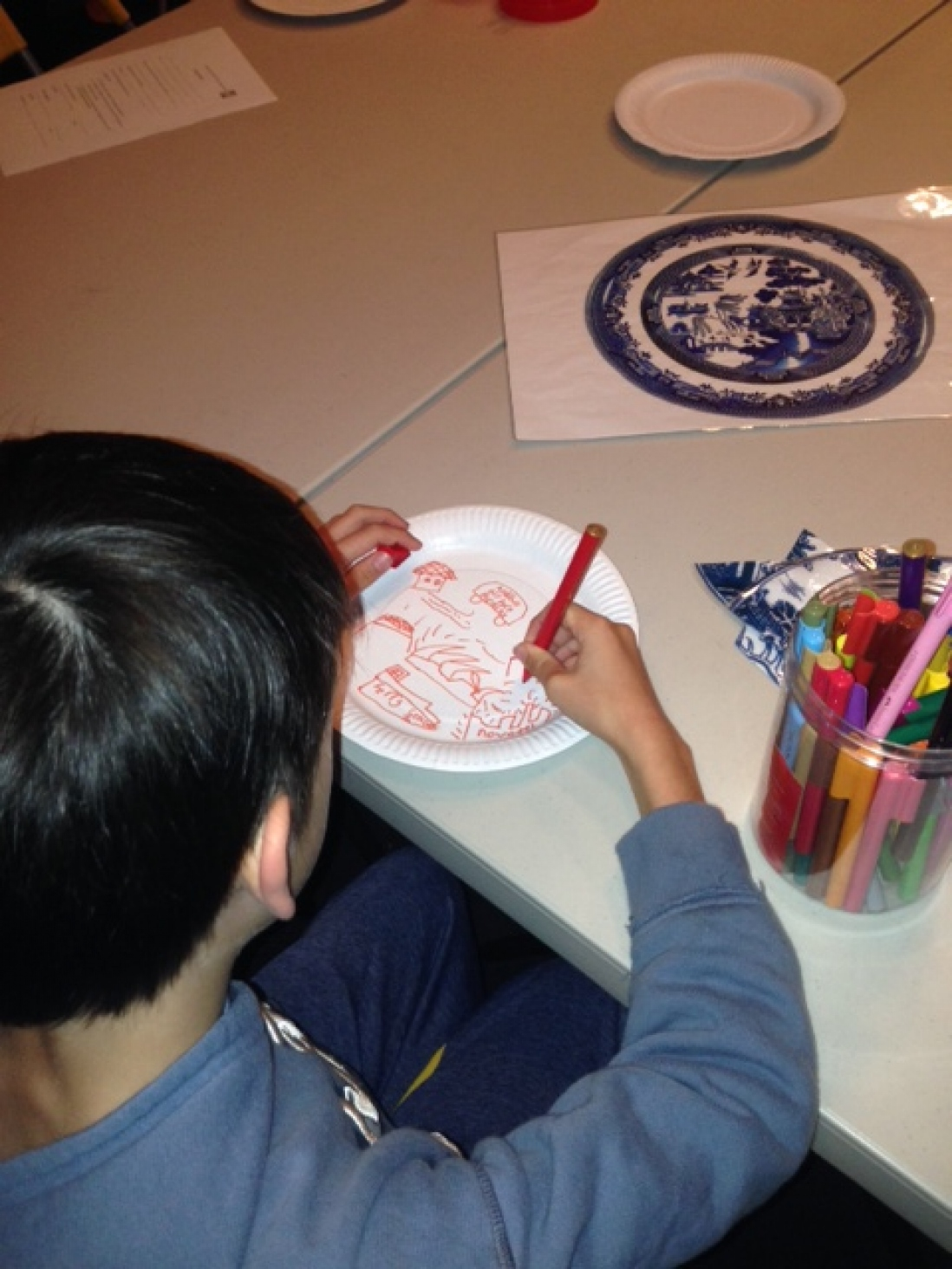 Back of boy's head, with his hand visible, drawing on paper plate with colour design.