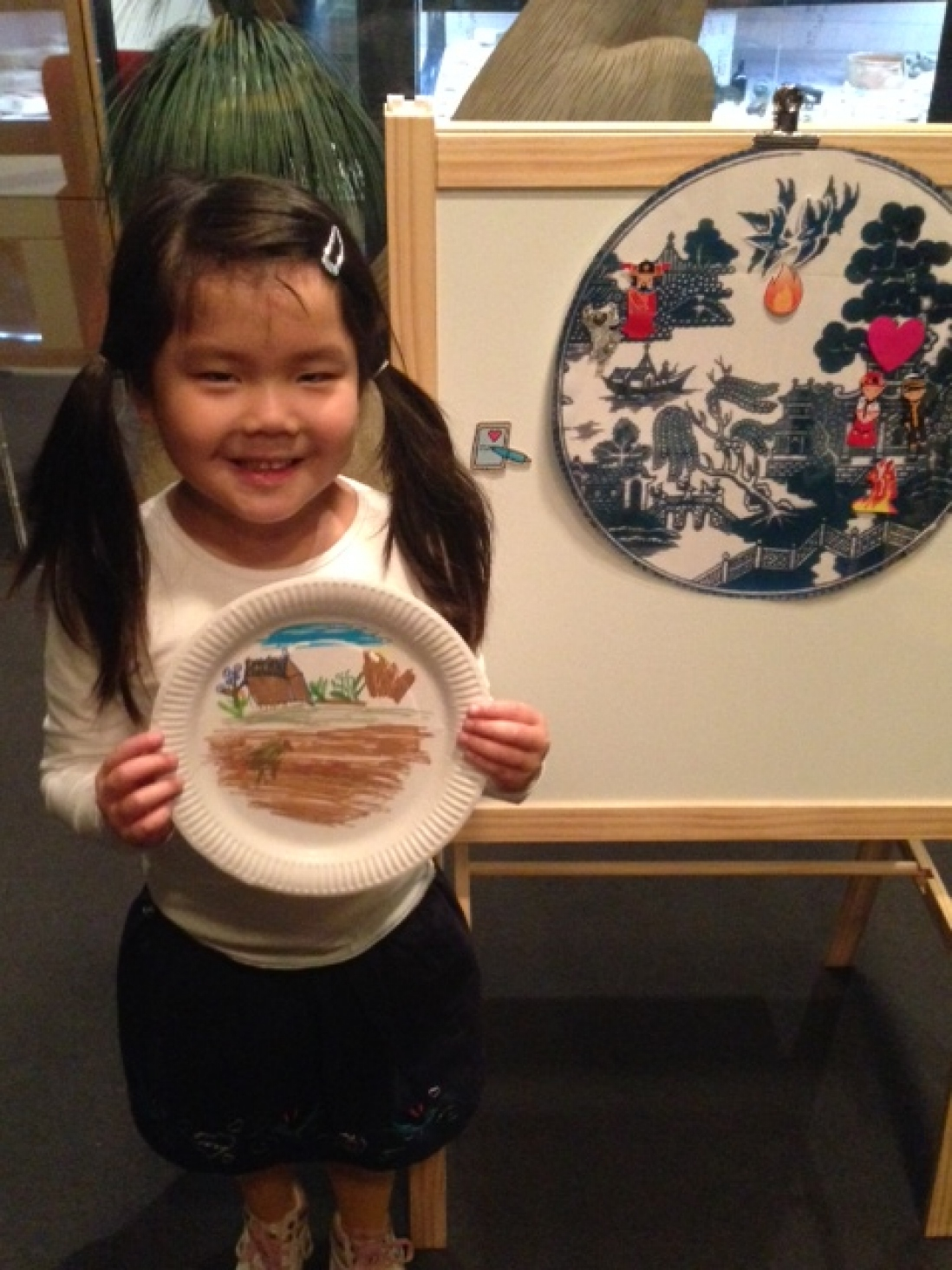 Young girl with pigtails holding up paper plate with colour design.