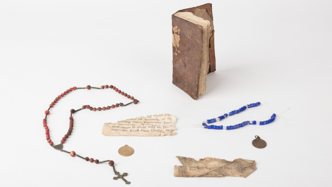 Collection of objects including rosaries, medals, a book and fragments of paper from a religious tract