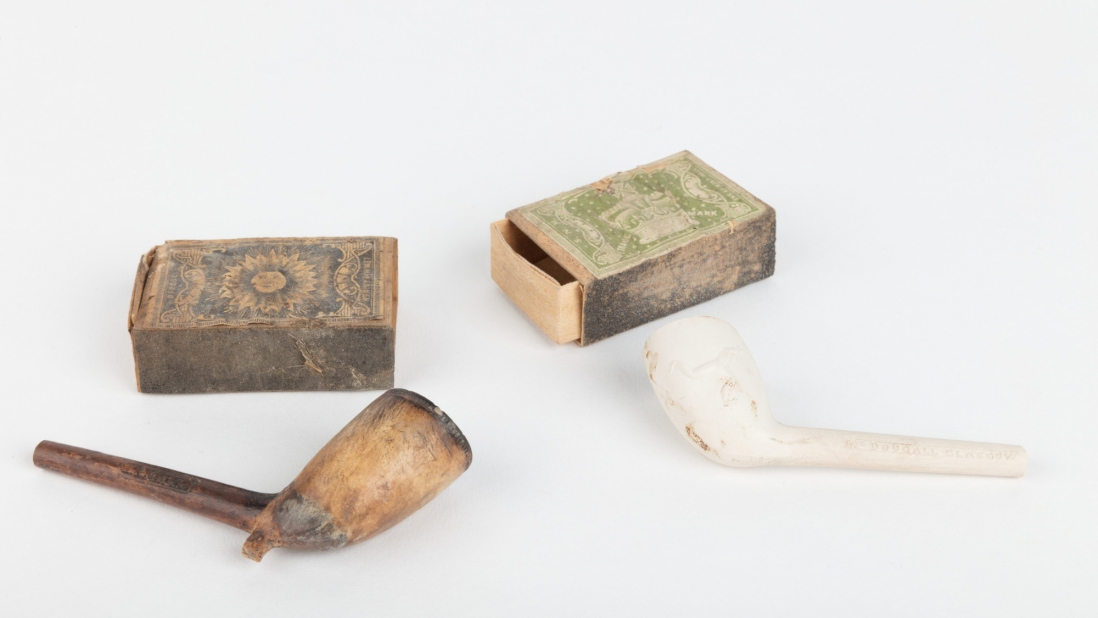2 matchboxes and 2 clay pipes.