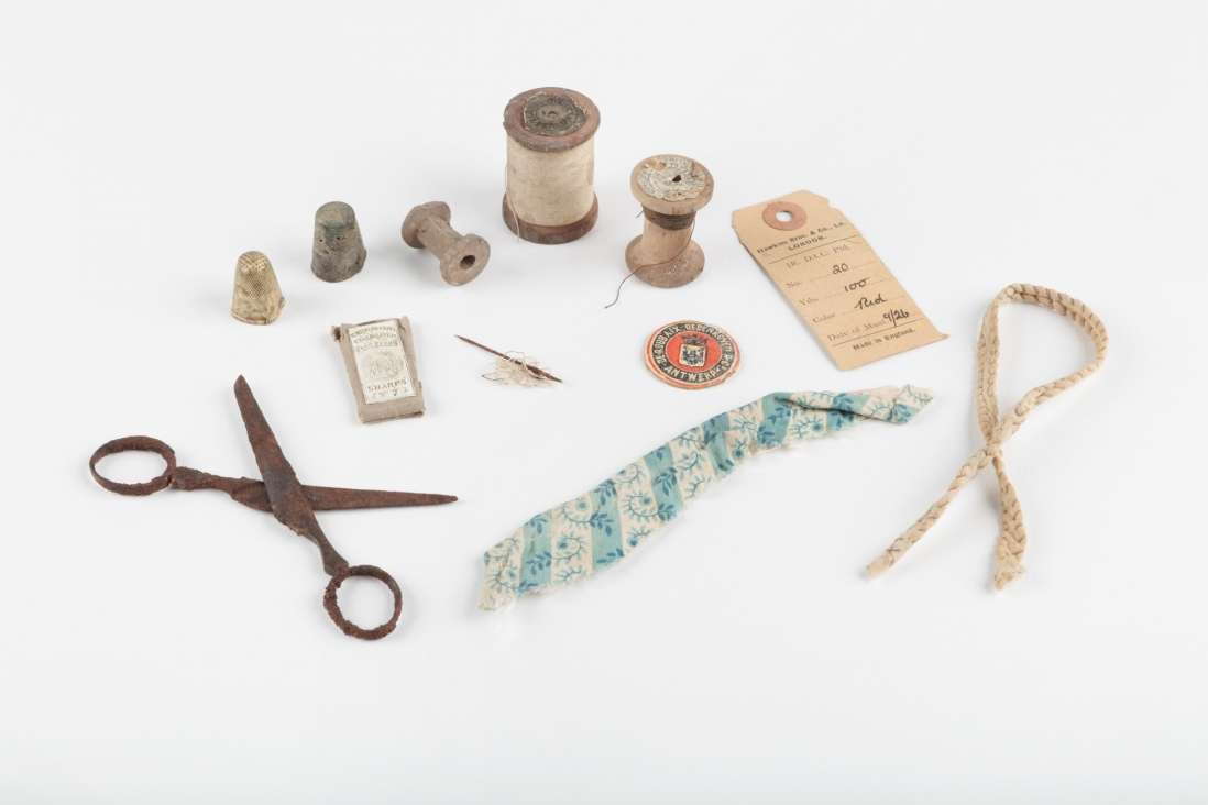 A selection of objects on a white background, including scissors and other sewing equipment.