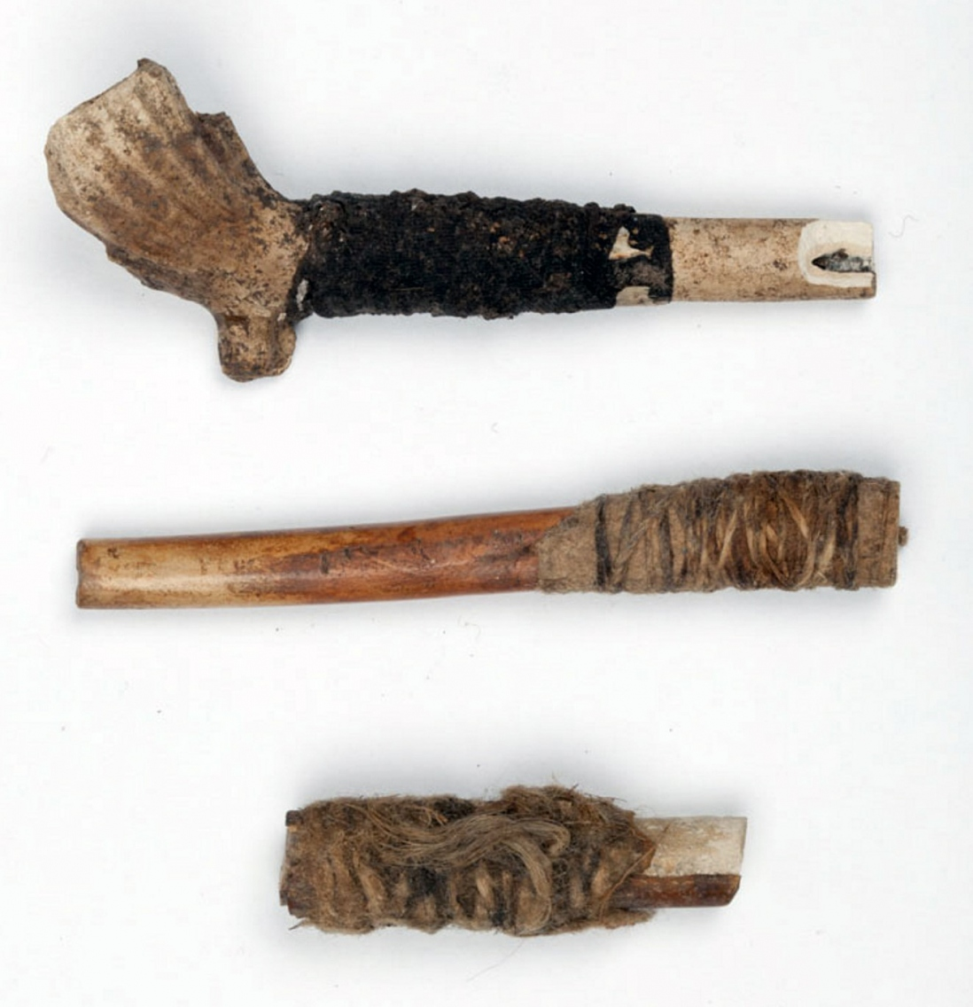Brown coloured clay pipes, top one complete, bottom two broken stems only, with twine bound around stems..