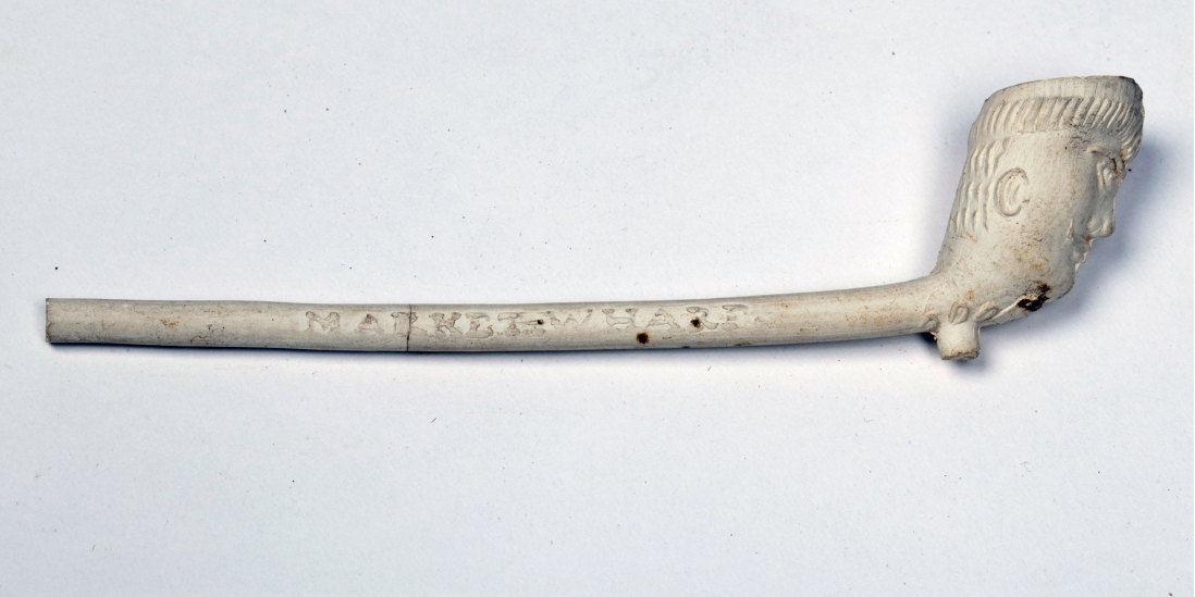 Slender-stemmed white clay pipe with carved bowl and lettering on stem.