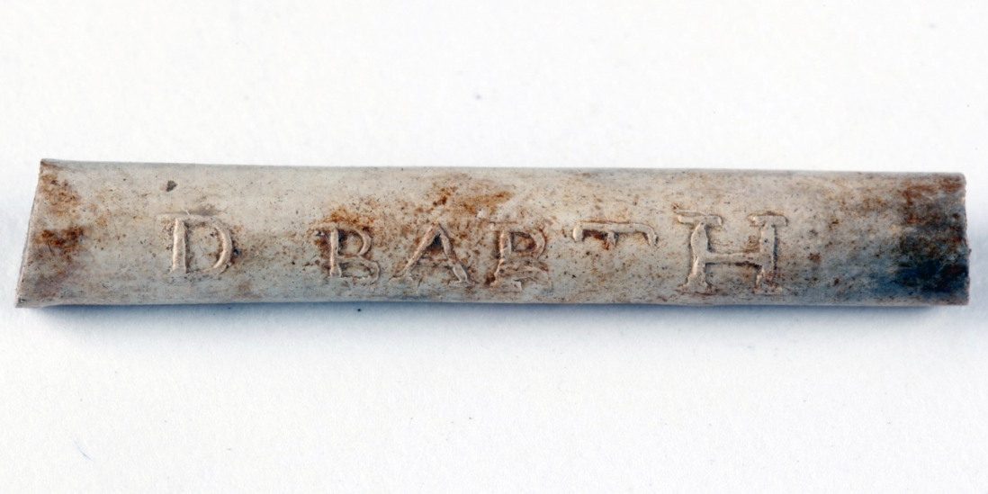 Close up of carved name on white clay pipe with orange stain.