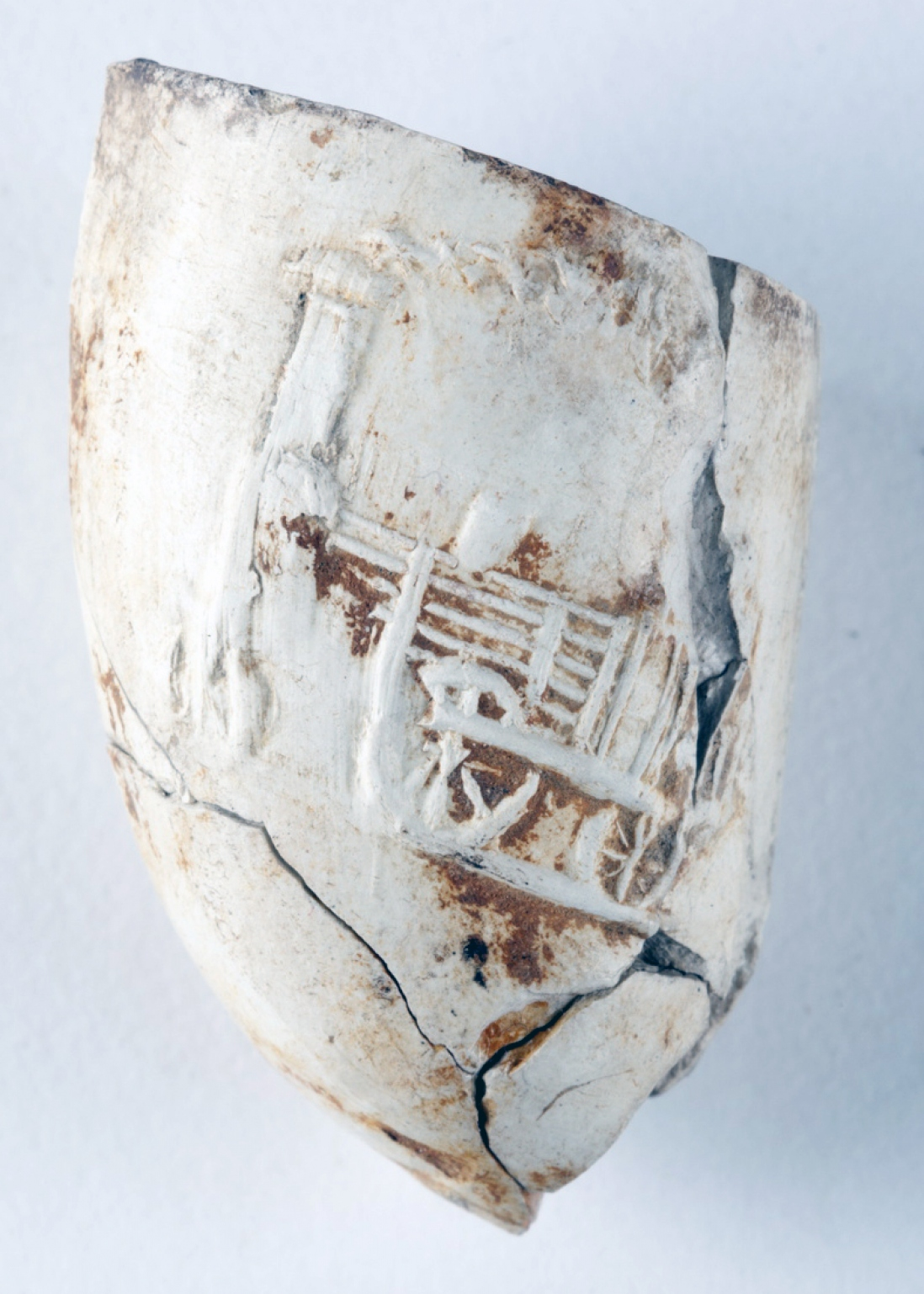Close up of carved locomotive on white clay pipe bowl.