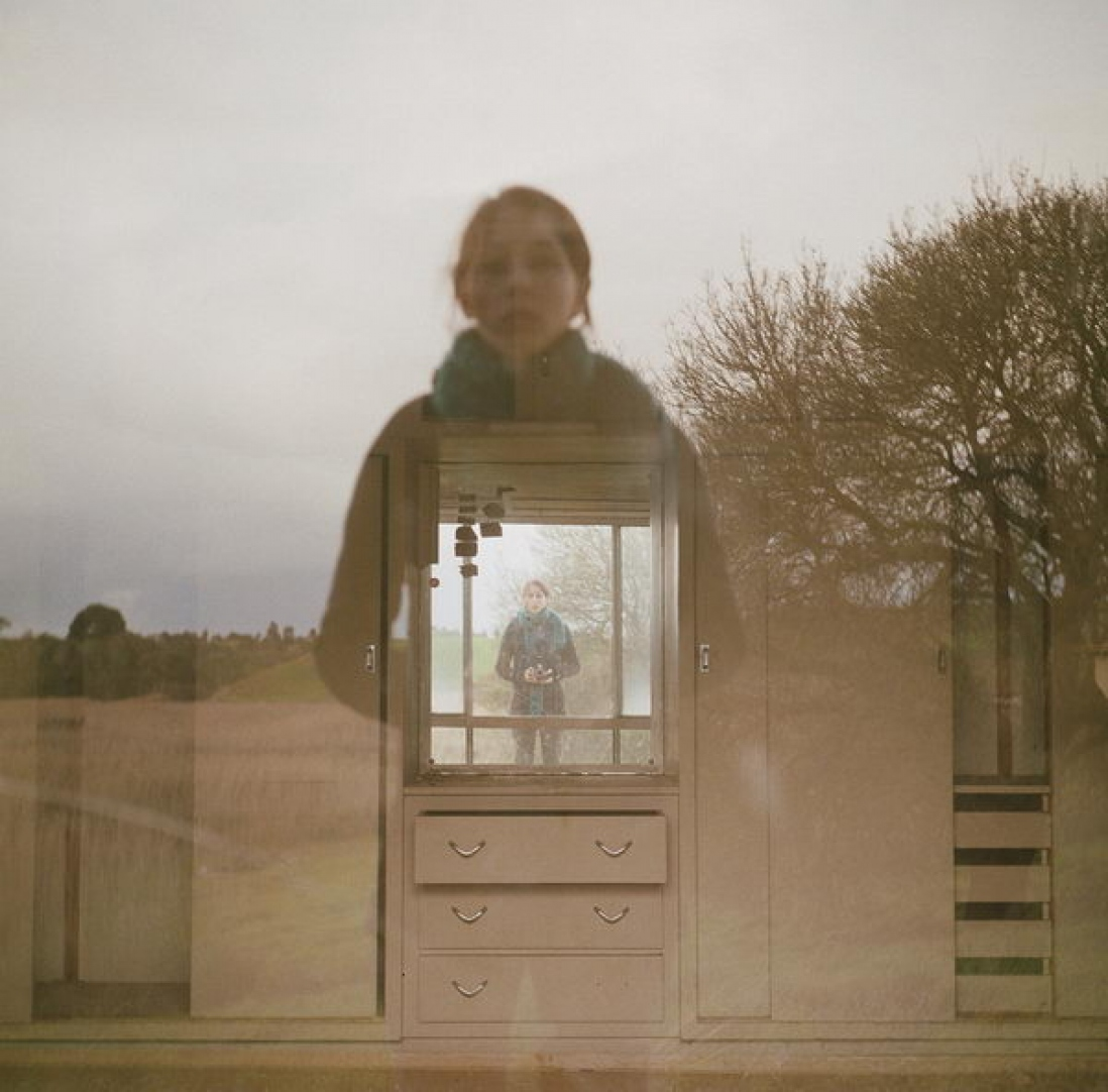 Photograph of reflection of photographer in window and in mirror in room beyond window.