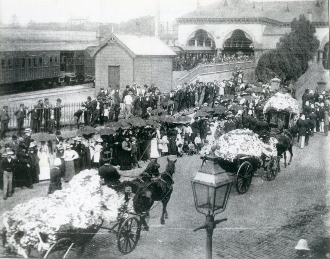 Black and white shot of funeral procession at station.