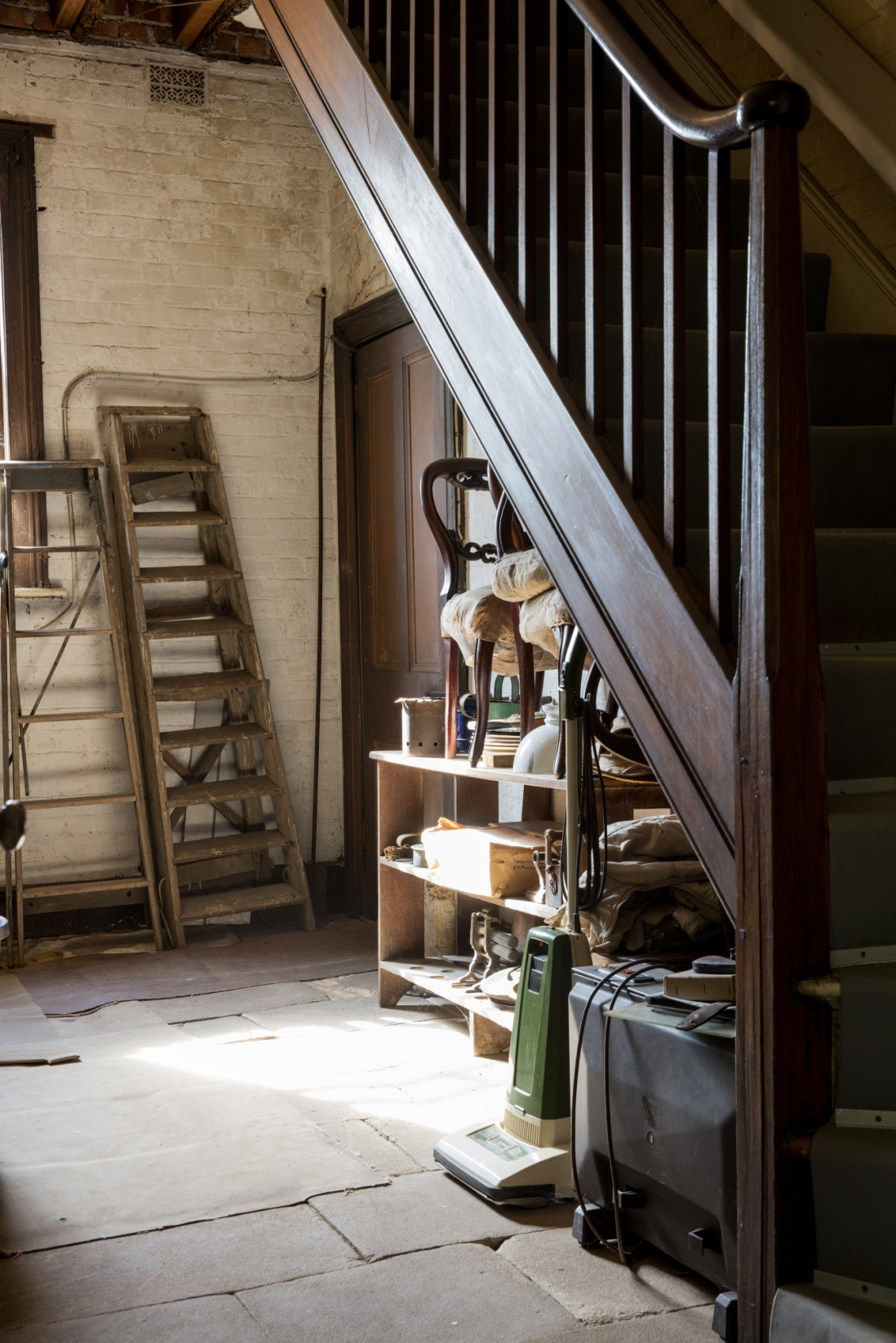 Equipment leaning against wall underneath wooden staircase.