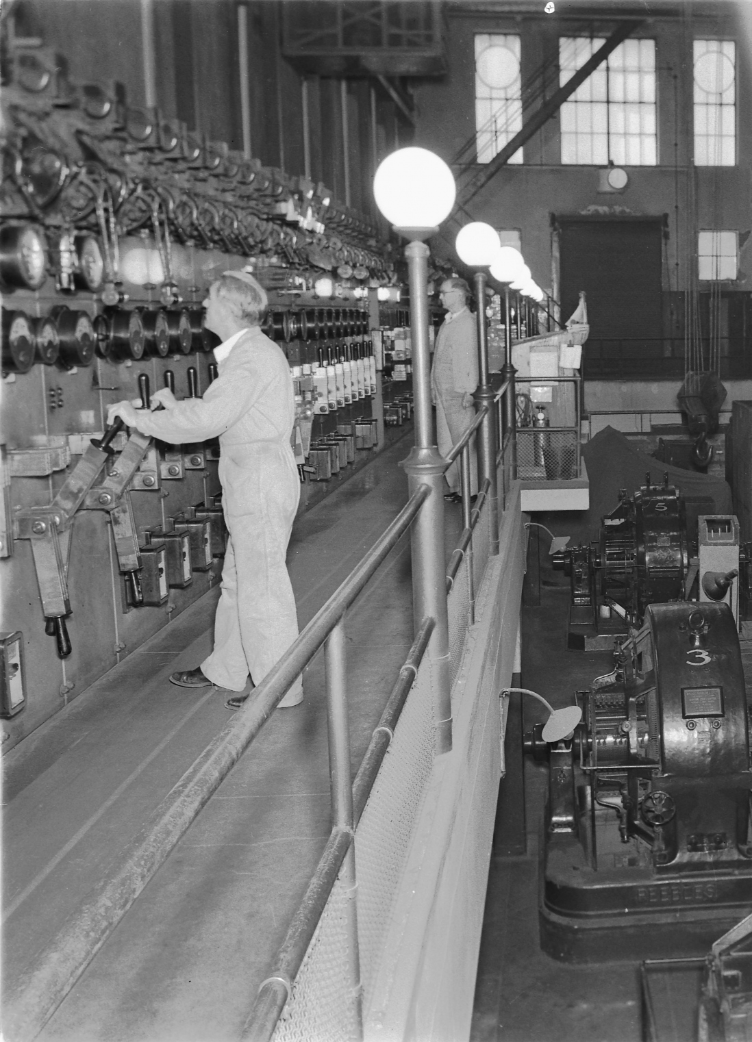 Man operating equipment standing on balcony with railing.