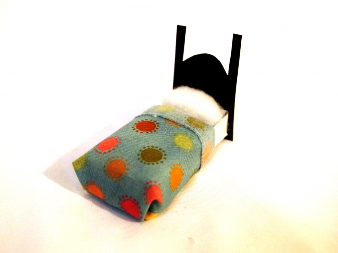 Completed matchbox mini-bed craft item with cardboard bedhead and patterned fabric cover.