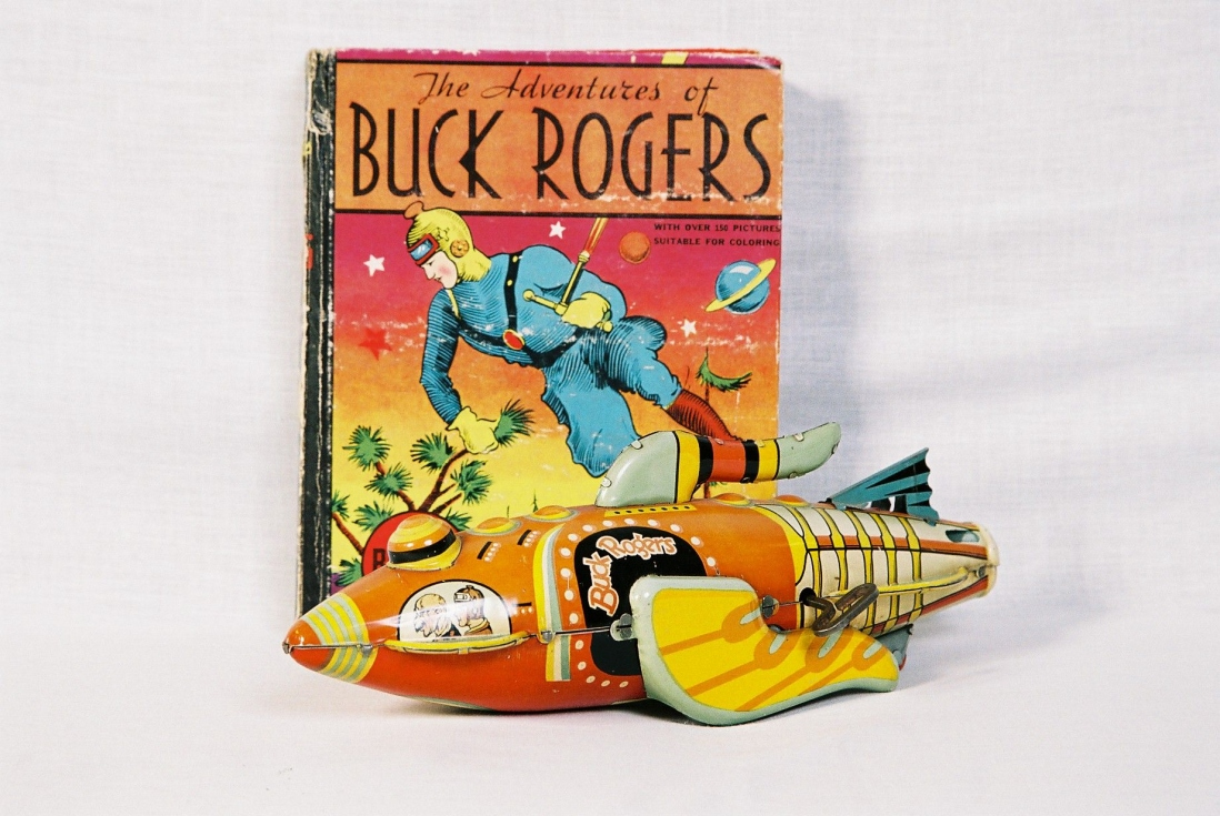 This is a colour photograph of a tin plate rocket ship toy and a small illustrated book about heroic comic character Buck Rogers