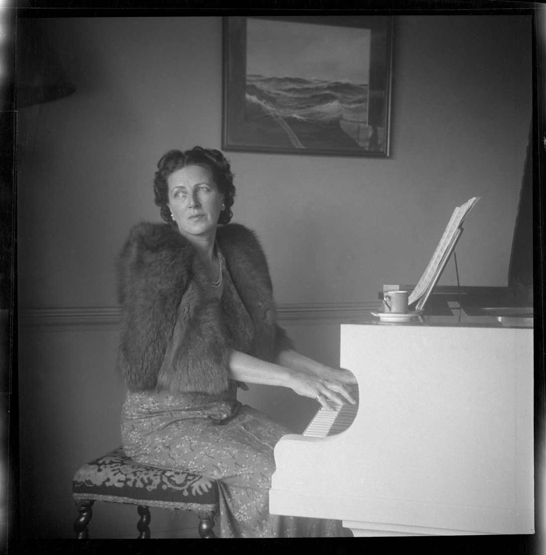 Black and white photo of woman seated at piano