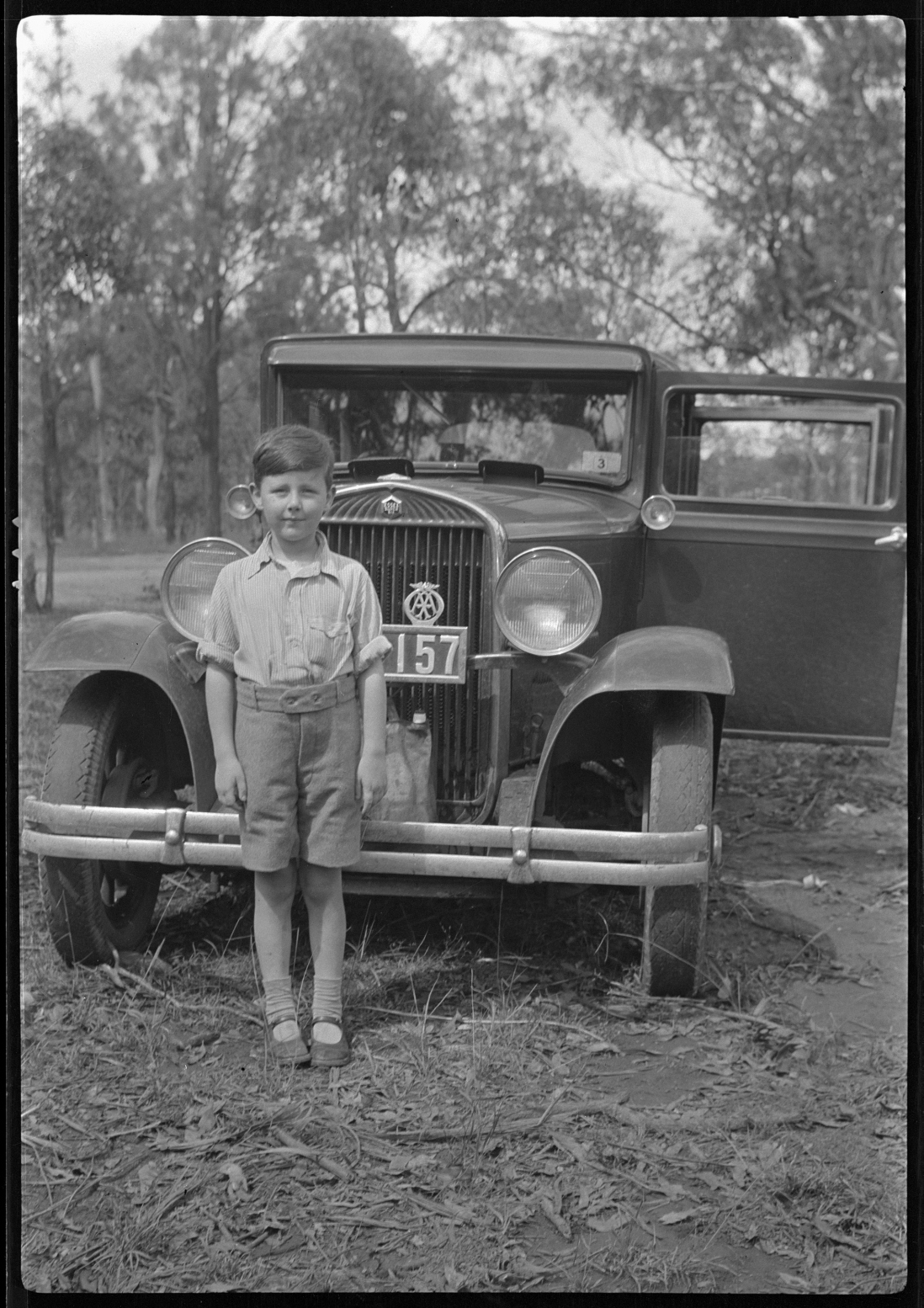 Black and white photo of boy standing in front of vintage car in bush setting.