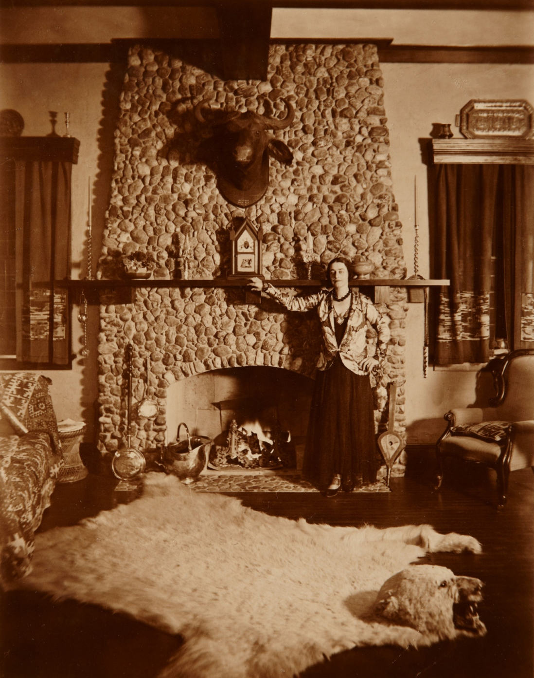 Mrs Muriel Mackay standing by the fireplace in the living room of Tinagroo homestead near Scone New South Wales, c1925