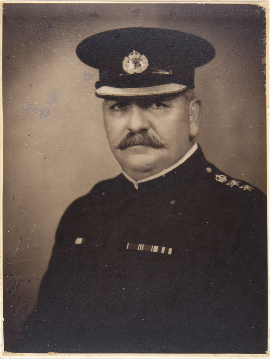 Moustached man in police uniform and cap.