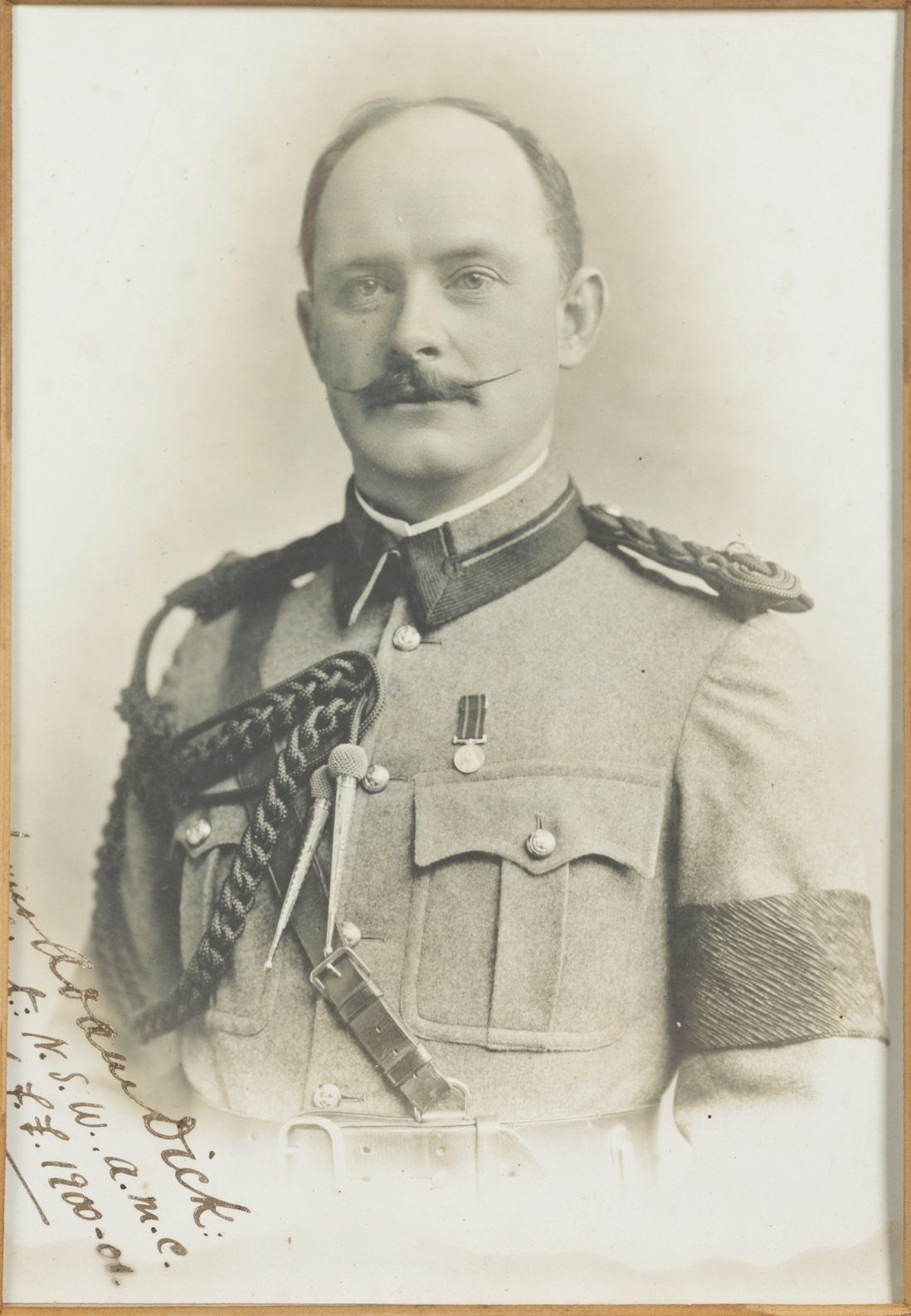 Black and white silver gelatin photo of man in dress uniform, with waxed moustache.