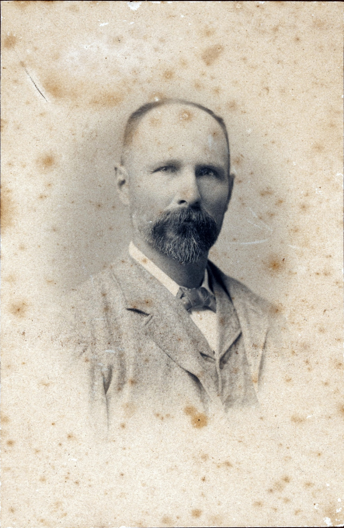 Discoloured and spotted black and white portrait of balding man with moustache and beard.