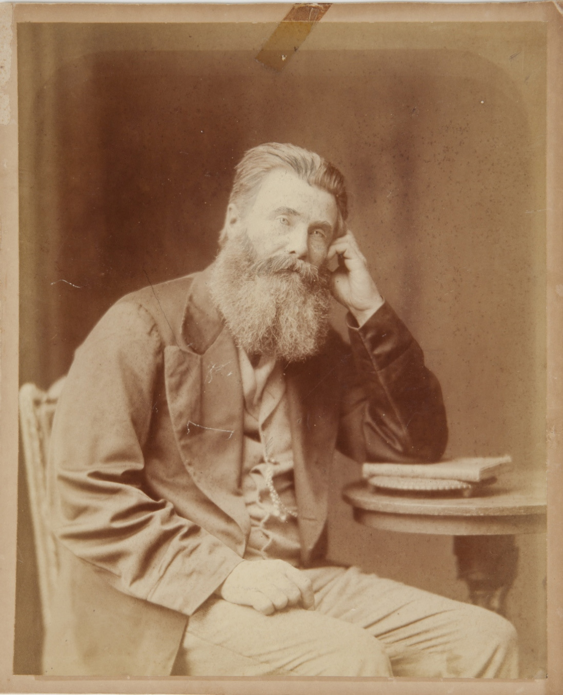 An albumen paper print Paris panel portrait photograph of bearded man seated next to a circular table, resting his left arm on a book on the table. He wears light coloured pants and waistcoat with darker coloured jacket.