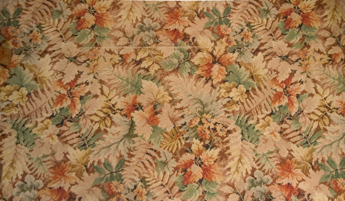 Close up of floral carpet in reds, greens and cream.