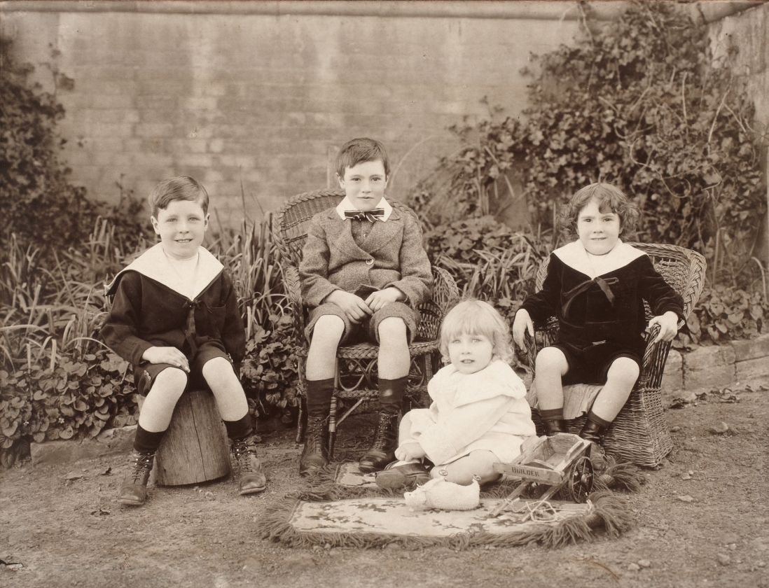 Black and white photograph of four children, one with toy sheep, in a walled garden