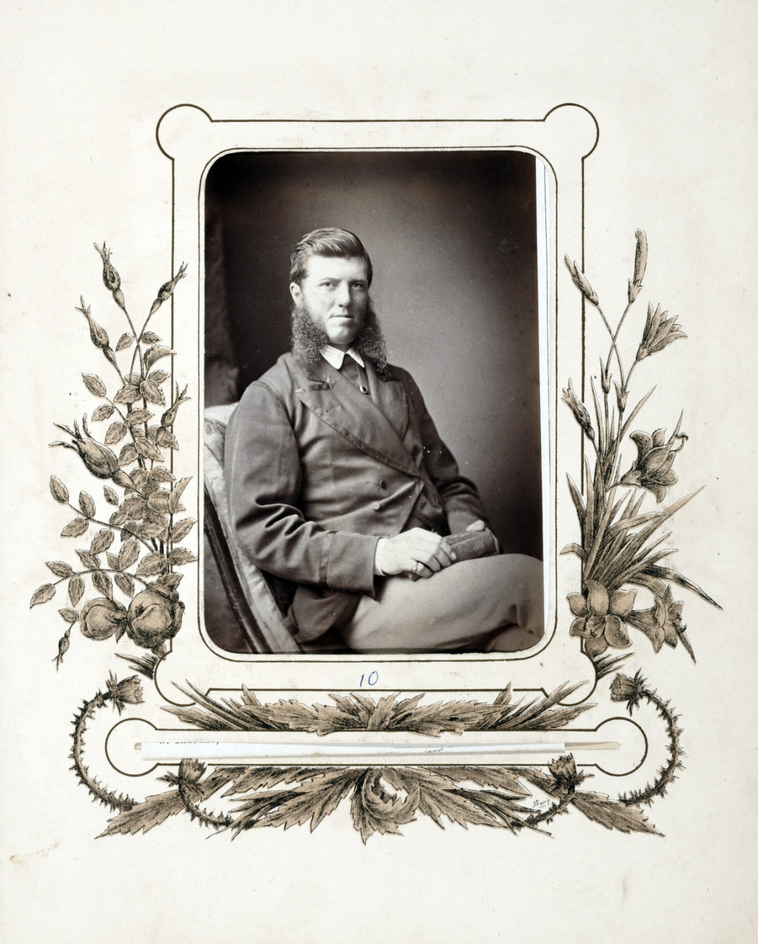 square cornered sepia toned portrait of man seated towards camera right and his face looks directly at the camera. The chair is armless and upholstered, and there is a length of dark fabric hanging behind his right shoulder.
