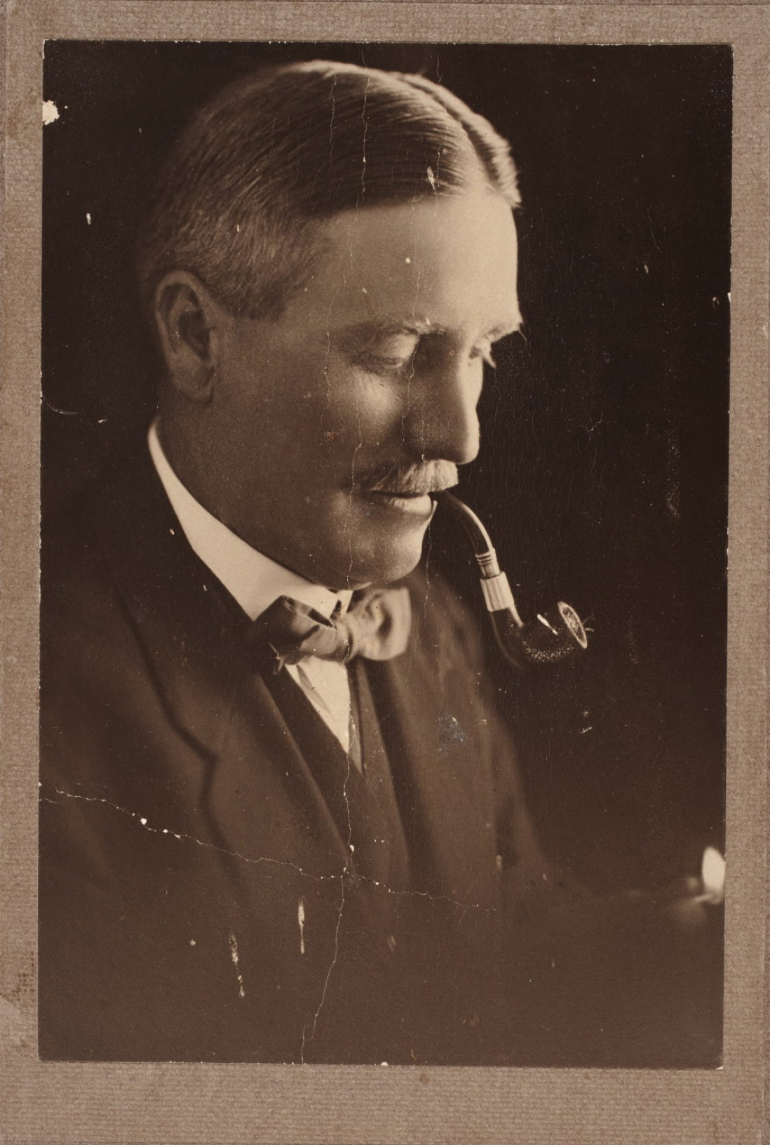 Portrait of man showing his right profile and smoking a pipe.